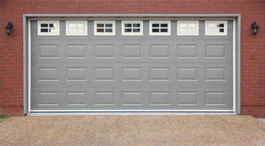 Garage with doors, brick wall and asphalt driveway Stock Photos