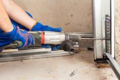 Garage doors installation. Worker drills a hole for the bolt. Garage doors installation. Worker drills a hole for the bolt royalty free stock image