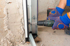 Garage doors installation. Worker use automatic screwdriver  to fix a bolt. Garage doors installation. Worker use automatic screwdriver  to fix a bolt Royalty Free Stock Photos