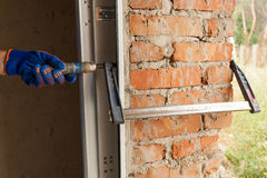 Garage doors installation. Workers install fasteners to hold the metal structure. Royalty Free Stock Photography