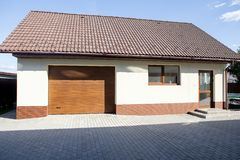 Garage garden house. Sliding gates. Hot sunny day. stock photos