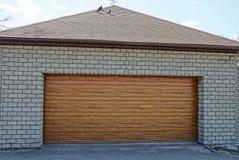 Garage grigio del mattone con i portoni marroni sulla via immagine stock