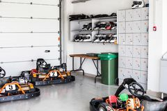 Garage for karting storage, shelves with helmets and storage boxes. Summer, active family fun or sports stock photos