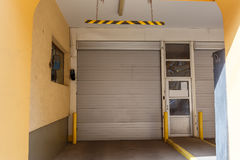 Garage lift gates in house, parking for cars in residential building. Garage lift gates in yellow house, gates of parking for cars in residential building Royalty Free Stock Images