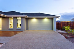 Garage with a long and wide concrete or stone yard in front at d