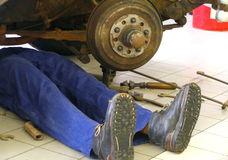 Garage-man,. Garage-man working under old car stock photography