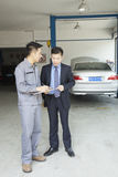 Garage Mechanic Explaining to Customer Stock Photo