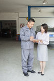 Garage Mechanic Explaining to Customer, Showing Her the Bill stock images