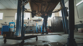 Garage mechanical workshop - mechanic checks bottom of car - lifted auto standing in automobile service. Wide angle Royalty Free Stock Image