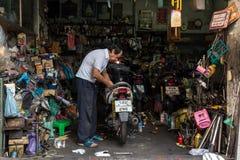 Garage owner repairing motorbike Royalty Free Stock Images