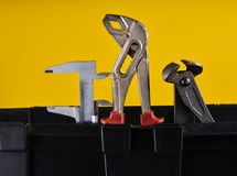 Garage plastic tool box with working tools isolated on a yellow. Nippers, wrench, caliper. stock image