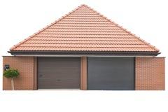 Garage pour deux voitures de brique rouge, le toit des tuiles rouges L'arbre se d?veloppe devant le garage D'isolement sur le fon photo stock