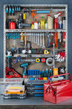 Garage rack. Garage tool rack with various tools and repair supplies on board and shelves Stock Image