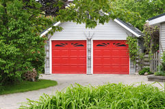 Garage with red doors. In green setting Royalty Free Stock Images