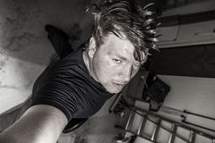 Garage rock selfie. A bass player standing in a garage glancing up at the camera in his hand with a stern look to his face Stock Image