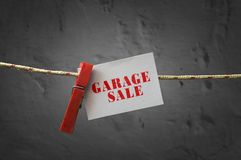 Garage sale card attached to a rope with clothes pins. On dark background Royalty Free Stock Photography