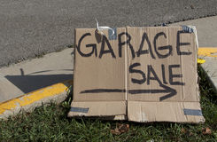 Garage sale hand made sign. Garage sale text with arrow written on cardboard and placed on grass next to the street Royalty Free Stock Photo