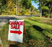 Garage sale sign on grass. Garage sale sign in grass with autumn trees on street Stock Image