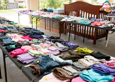 Garage sale tables with clothing. Tables of clothing and other baby goods on display in a suburban garage stock photos