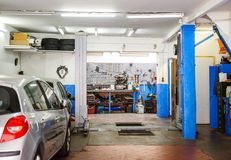 Garage service entrance with tools, elevator and car Stock Images