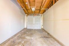 Garage vide avec la porte concrète de plancher et de garage fermée Photo libre de droits