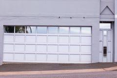 Garage Visitors Doors Entrance. Double garage door and pedestrian visitors door cream grey reflective decor road entrance stock photos