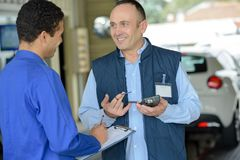 Garage worker receiving delivery Royalty Free Stock Image