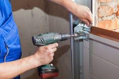 Garagedörrinstallation Arbetare som installerar lyftande systemet i metallprofil med skruvmejsel royaltyfria bilder