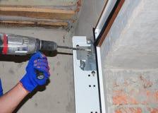 Garagedörrinstallation & utbyte Installera garagedörren & borrandehålet för fasta garagedörrvårar royaltyfri fotografi