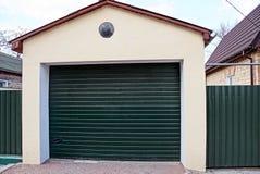 Garagem com portas verdes fechados e peça da cerca na rua perto da estrada imagens de stock royalty free