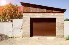 Garagem de pedra com a porta das cortinas de rolo perto da casa no ensolarado Imagens de Stock