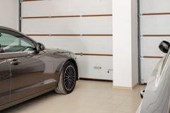 Garagem home para dois veículos interiores Limpe os carros luxuosos estacionados em casa Portas de controle remoto automáticas O  fotos de stock royalty free