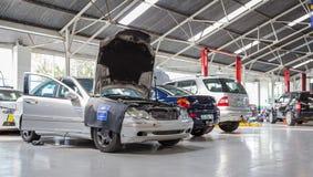 Garagereparatiewerkplaats met auto's klaar om worden bevestigd stock foto