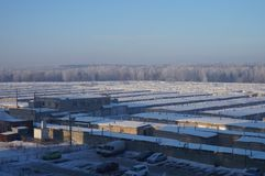Garages on the background of the winter forest. Winter cold sky, frost royalty free stock photo