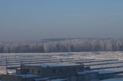 Garages on the background of the winter forest. Winter cold sky, frost stock photos