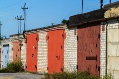 Garages de brique avec les portes rouges en métal de la coopérative de garage Photographie stock libre de droits