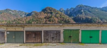 Garages. A line of garages with doors of different colours. On the background the Alps of the town of Cave del Predil, Friuli, Italy Royalty Free Stock Photo