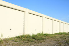 Garages. White garages - warehouses with metal gates and blue sky above stock photo