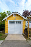 Garaje amarillo acogedor con las puertas blancas Fotos de archivo libres de regalías