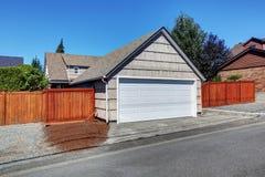 Garaje blanco de la puerta y patio trasero cercado imagen de archivo libre de regalías