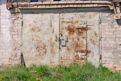 Garaje blanco viejo del ladrillo con la puerta oxidada fotos de archivo