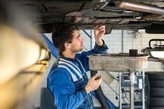 Garaje de Examining Car At del mecánico Foto de archivo
