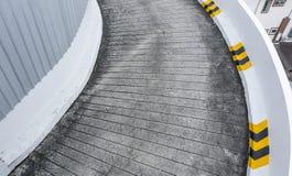 Garaje del coche del estacionamiento de la rampa del camino concreto de la rampa del garaje con las líneas amarillas en el lado Fotografía de archivo
