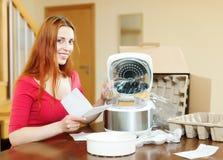 Garantía alegre de la lectura de la mujer para la nueva slo-cocina Imagenes de archivo