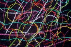 Garatujas coloridos do pastel no papel preto foto de stock royalty free