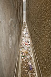 Garbage Alley. A gap between two buildings that is too small for a person to fit, but is filled with garbage Royalty Free Stock Images