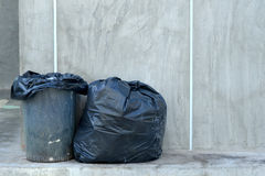 Garbage bag beside the bin. A black garbage bag is placed beside the bin Royalty Free Stock Photos