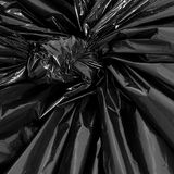 Garbage Bag Detail. A black plastic garbage bag, knotted at the top Royalty Free Stock Photo