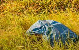 Garbage bag dumped in a berm Royalty Free Stock Photo