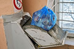 Garbage bag full of a garbage lying in a lid of a home garbage chute. In Moscow dwelling house Stock Image
